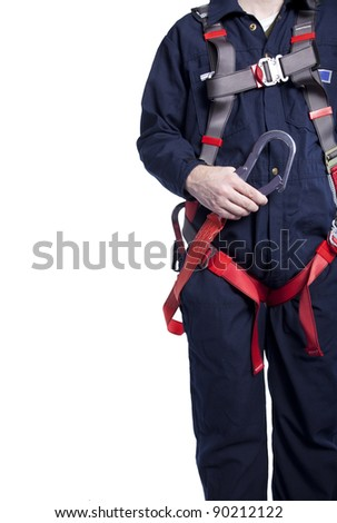 worker wearing blue coveralls and a fall protection harness and lanyard for work at heights - stock photo
