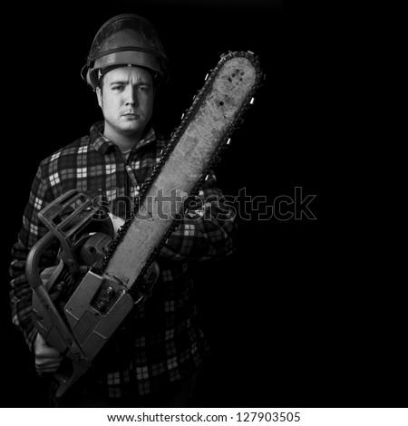 worker wearing helmet with chainsaw black and white with copy space - stock photo