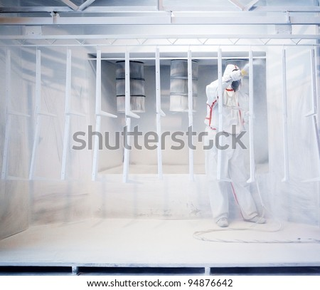 Worker wearing protective wear performing powder coating of metal details in a special industrial camera - stock photo