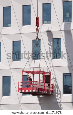 Worker wearing safety harness and helmet in a hoist basket