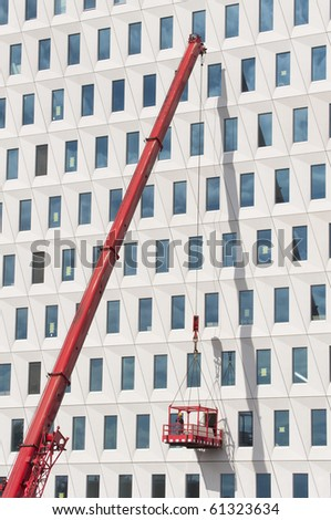 Worker wearing safety helmet and safety harness on a hoist basket hoisted by a crane - stock photo