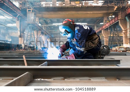 worker weld metal in factory and sparks
