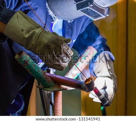 Worker welded iron pipe by argon welding machine - stock photo