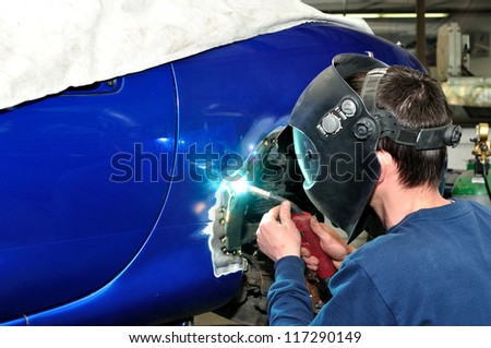 Worker welding car. - stock photo