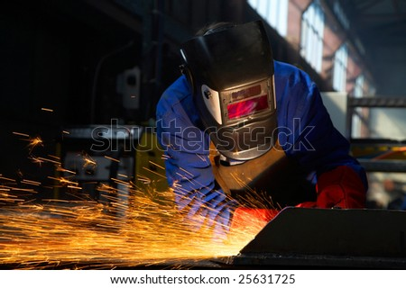 worker welding/grinding metal and sparks spreading - stock photo