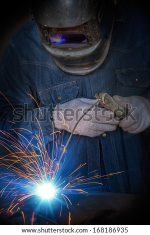 Worker welding the steel part for repair in an industrial factory.