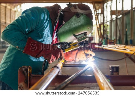 Worker welding the steel structure - stock photo