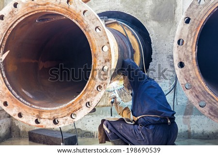 Worker welding two big pipes in at the exit from trench - stock photo