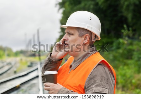 Worker with a coffee and cell phone on the railway - stock photo