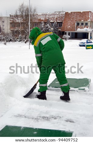 worker with a shovel clears snow in winter - stock photo