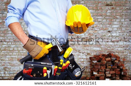 Worker with a tool belt. Over brick wall background. - stock photo