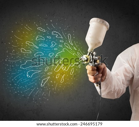 Worker with airbrush gun paints colorful lines and splashes concept - stock photo