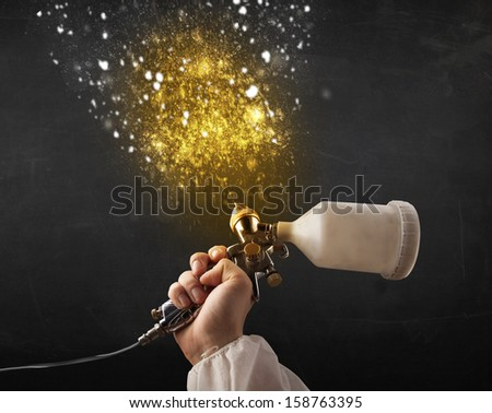 Worker with airbrush painting with glowing golden paint and particles - stock photo