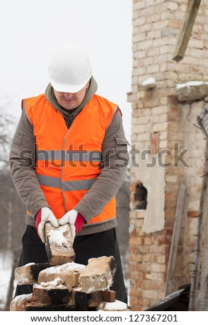 Worker with brick in hands near the burned old house - stock photo