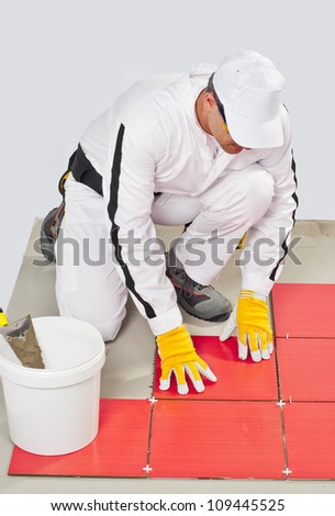 worker with bucket adhesive apply red tiles - stock photo