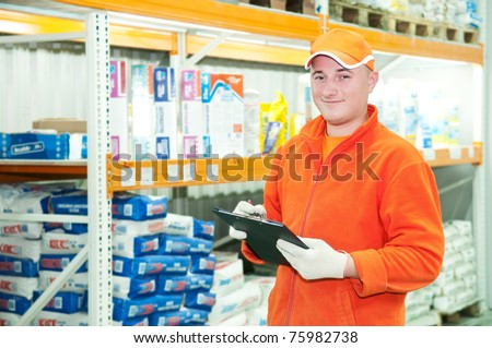 worker with cardboard at warehouse goods depot - stock photo