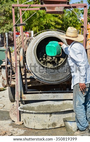 Worker  with  cement mixer at the construction site - stock photo