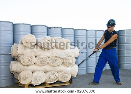 worker with fork pallet truck stacker in warehouse loading fabric rolls - stock photo