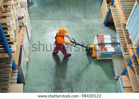 worker with fork pallet truck stacker in warehouse loading furniture panels - stock photo