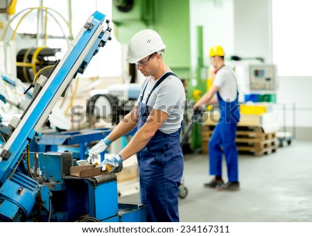 worker with goggles and helmet on the machine - stock photo