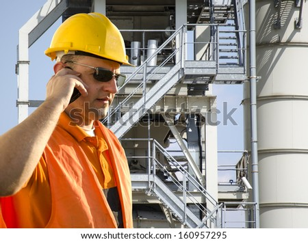 worker with helmet and sunglasses talking on mobile phone in front of industrial plant - stock photo