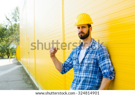 worker with helmet and yellow plaid shirt near a wall