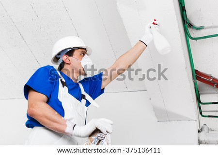 worker with helmet, gloves and mask spraying ceiling with spray bottle on wooden vintage ladder, bottom view