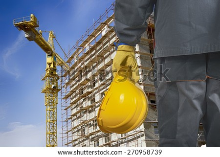 worker with helmet in front of construction scaffolding and construction crane - stock photo