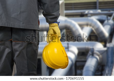 worker with helmet in front of production hall  - stock photo