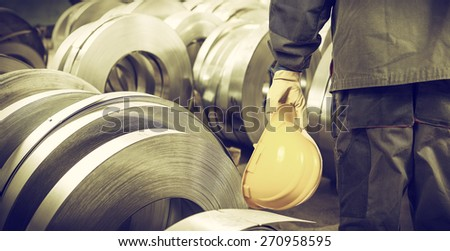 worker with helmet in production hall in front of steel sheet metal rolls, filters added to photo for vintage look - stock photo