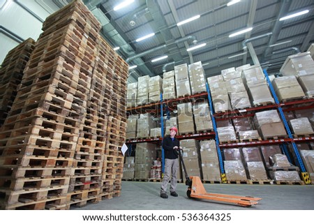 worker with order at stack of wooden pallets in storehouse