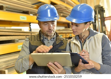 Worker with overseer controling stock in warehouse - stock photo