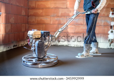 Worker with power trowel tool finishing concrete floor, smooth concrete surface at house construction - stock photo