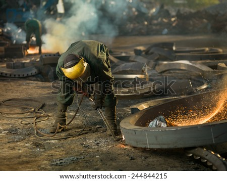 worker with protective equipment welding metal - stock photo