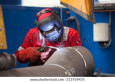 worker with protective equipment welding pipe