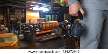 Worker with protective headphone at man hands at industrial factory - stock photo