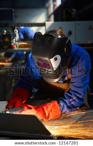 worker with protective mask and gloves grinding/welding metal and sparks spreading - stock photo