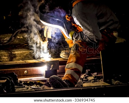 worker with protective mask and gloves welding train rail - stock photo