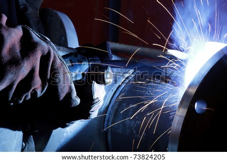 Worker with protective mask weld metal in industrial environment and sparks spread - stock photo