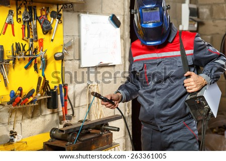 worker with protective mask welding metal  at  construction home studio