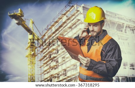 worker with protective uniform in front of construction scaffolding and construction crane - toned image, retro film filtered in instagram style - stock photo