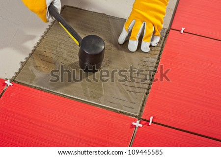 Worker with rubber hammer install glass tiles with tile adhesive. - stock photo