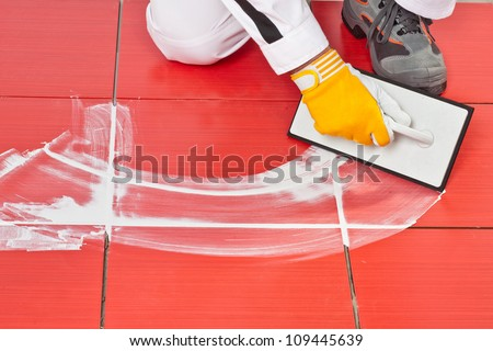 worker with rubber trowel applying white grout on red tiles on floor - stock photo