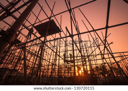 worker with scaffold near sunset - stock photo