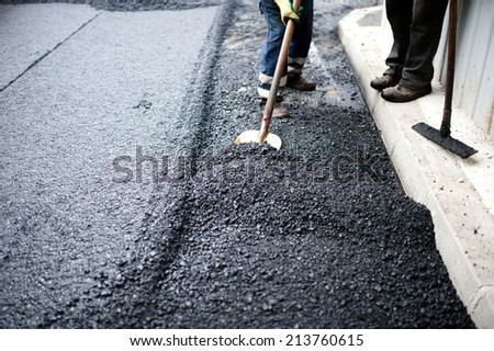 worker with shovel doing manual labor at road construction with asphalt and fresh bitumen
