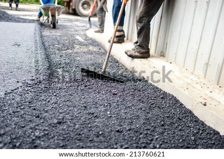 worker with special tool working with fresh asphalt and bitumen - stock photo