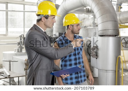 Worker with supervisor inspecting industrial area