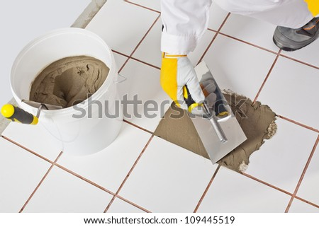 Worker with trowel repairs old white tiles with tile adhesive - stock photo