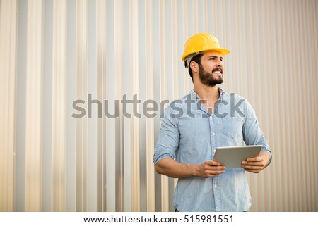 worker with yellow helmet and jeans shirt near a industrial wall, checking the stage of the project