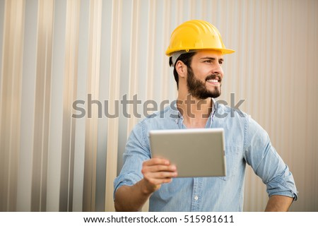 worker with yellow helmet and jeans shirt near a industrial wall, using a tablet to see the project